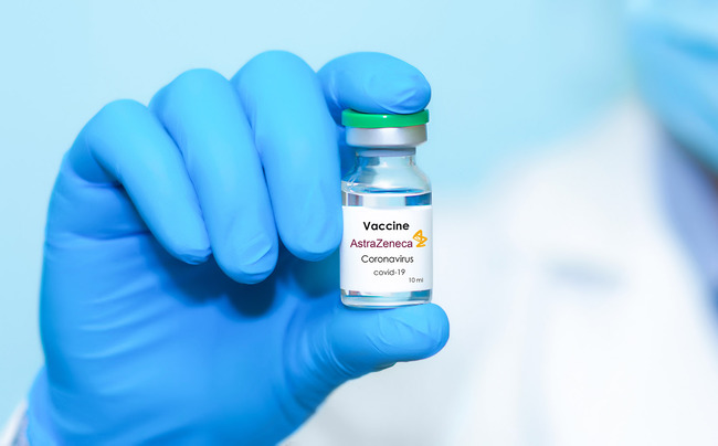 Vaccine ampoule is held in hand (Source: Stanislav Sukhin/Shutterstock.com)